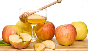 Apples surrounding a bowl of honey with a honey dipper