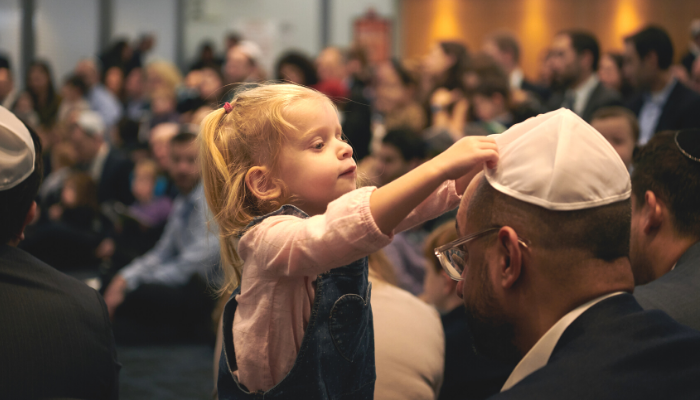 Young girl placing a kippah on her father's head