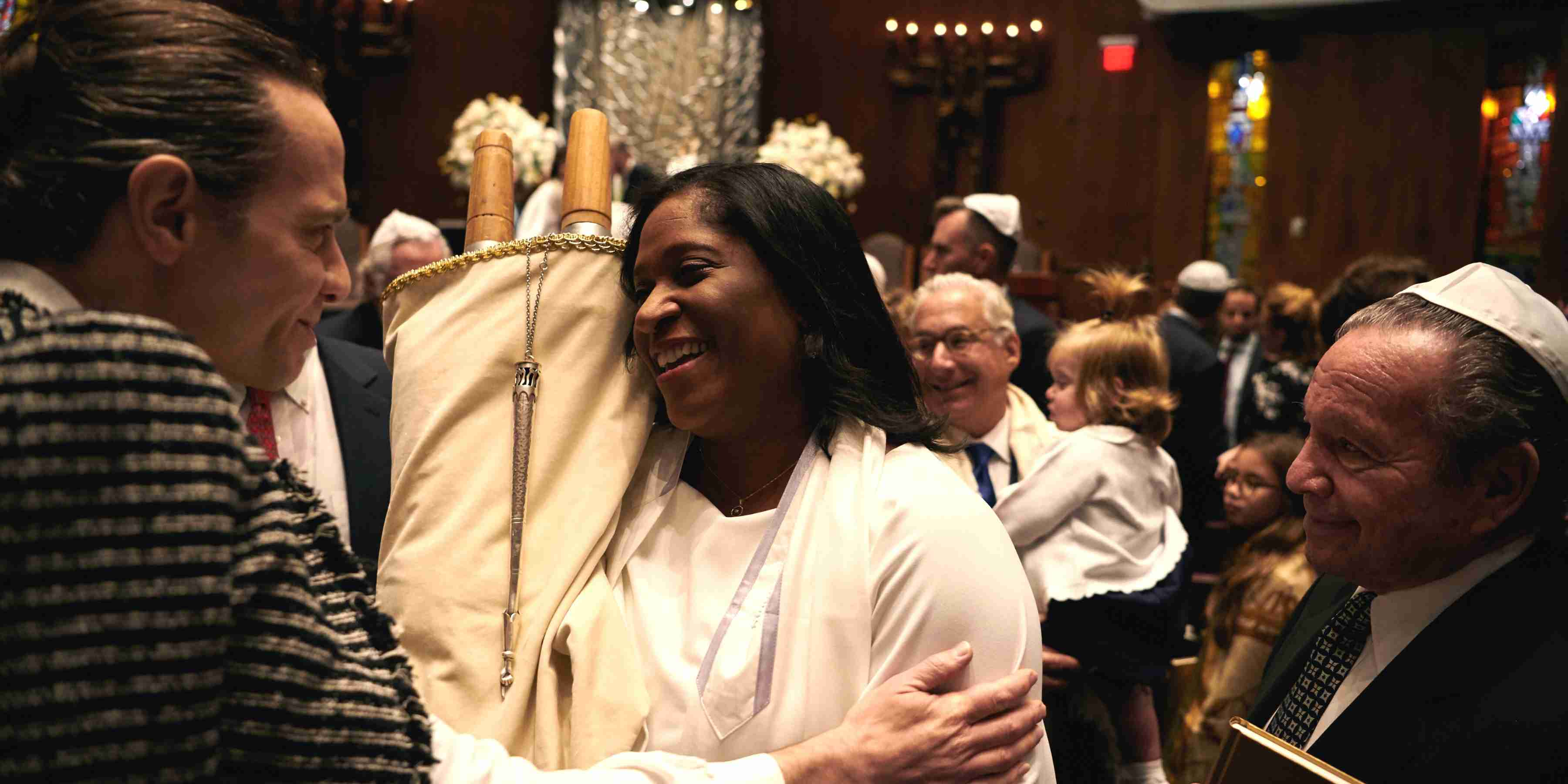 Woman carrying a Torah through the sanctuary