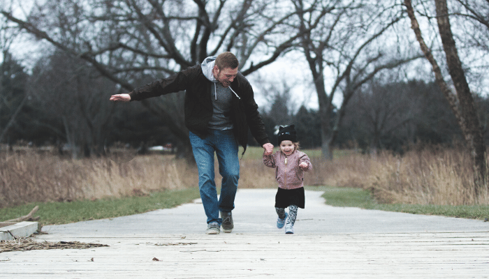 Father and daughter holding hands and running on a sidewalk