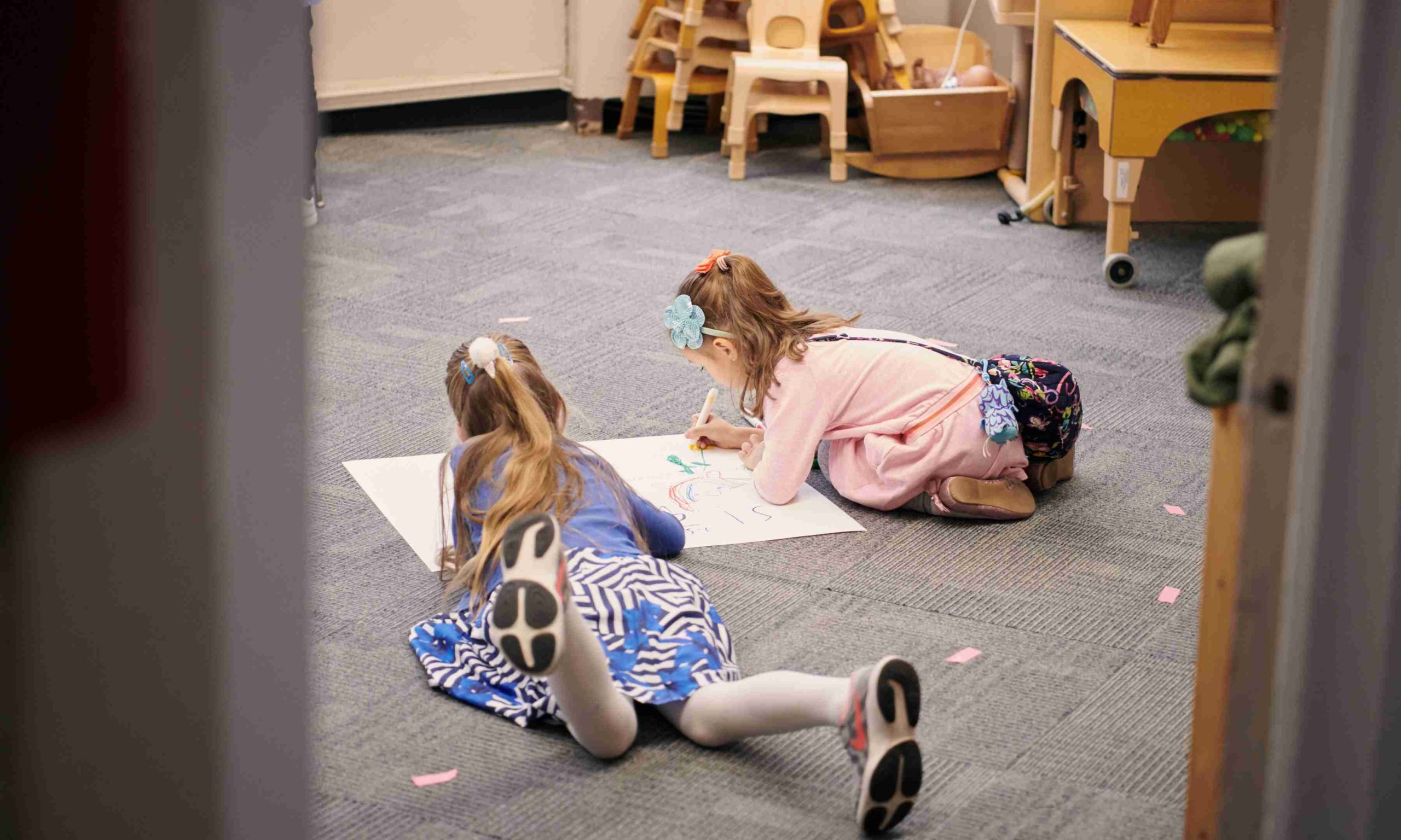 Two girls coloring on a classroom floor